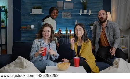 Pov Of Multi-ethnic Friends Gathering On Sofa Late At Night During Apartment Party Talking On Online