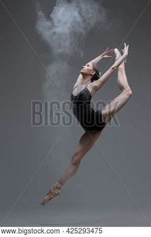 Skilled Ballerina Dancing Leaping Against Gray Background