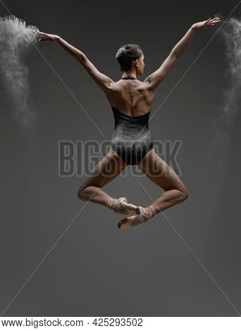 Backview Shot Of Jumping Ballerina With Outstretched Arms