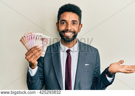 Handsome hispanic business man with beard holding turkish lira banknotes celebrating achievement with happy smile and winner expression with raised hand