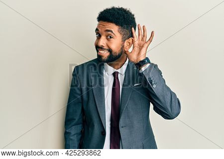 Handsome hispanic man with beard wearing business suit and tie smiling with hand over ear listening an hearing to rumor or gossip. deafness concept.
