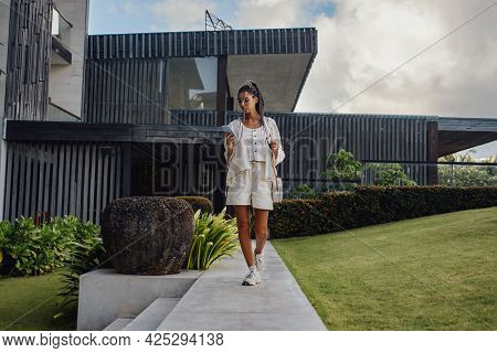 Woman With Phone Walking In Courtyard Of Mansion