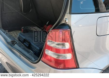 Taillight Of A Silver Hatchback Car And Open Trunk With Repair Tool Box. Summer Travel And Car Jorne