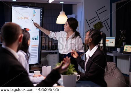 Multi Ethnic Businesspeople Brainstorming Company Ideas Checking Graphs Statistics Using Tv Standing