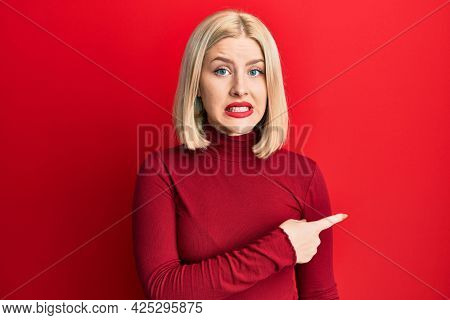 Young blonde woman wearing casual clothes pointing aside worried and nervous with forefinger, concerned and surprised expression