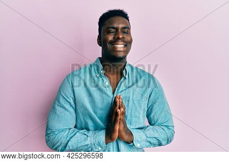 Handsome black man wearing casual clothes begging and praying with hands together with hope expression on face very emotional and worried. begging.