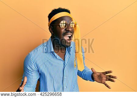 Handsome black man drunk wearing tie over head and sunglasses crazy and mad shouting and yelling with aggressive expression and arms raised. frustration concept.