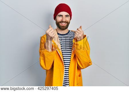 Caucasian man with beard wearing yellow raincoat doing money gesture with hands, asking for salary payment, millionaire business