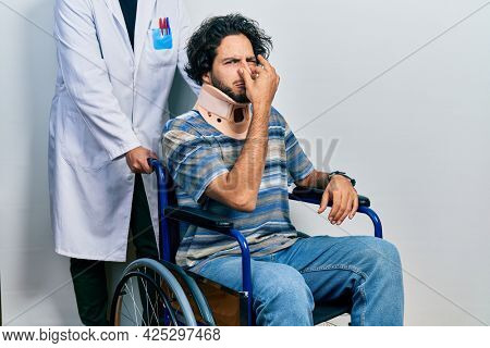 Handsome hispanic man sitting on wheelchair wearing neck collar smelling something stinky and disgusting, intolerable smell, holding breath with fingers on nose. bad smell