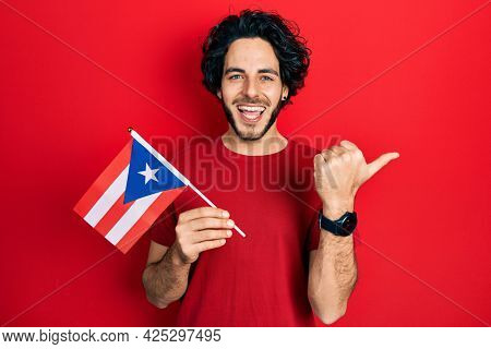Handsome hispanic man holding puerto rico flag pointing thumb up to the side smiling happy with open mouth