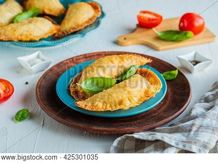 Chebureks Or Pasties, Traditional Deep-fried Meat Pies On A Blue Plate On A Light Concrete Backgroun