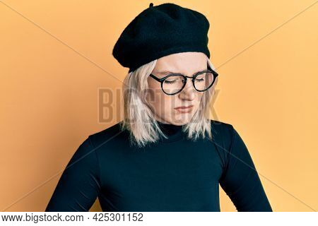 Young blonde girl wearing french look with beret with hand on stomach because indigestion, painful illness feeling unwell. ache concept.