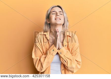Young blonde girl wearing casual clothes begging and praying with hands together with hope expression on face very emotional and worried. begging.