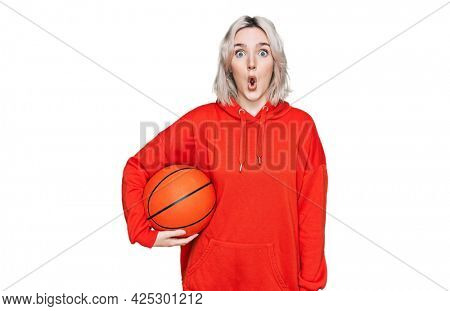 Young blonde girl holding basketball ball scared and amazed with open mouth for surprise, disbelief face