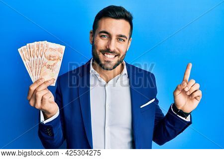 Young hispanic businessman wearing business suit holding turkish lira banknotes smiling happy pointing with hand and finger to the side