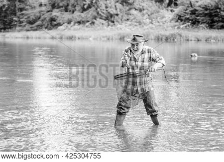 Fisherman Fishing Equipment. Hobby Sport Activity. Fisherman Alone Stand In River Water. Man Senior