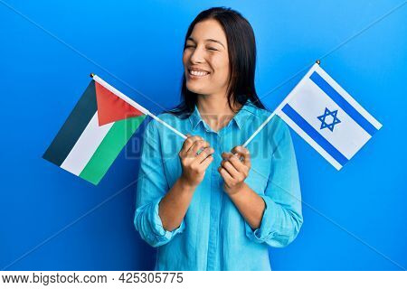 Young latin woman holding palestine and israel flags winking looking at the camera with sexy expression, cheerful and happy face.