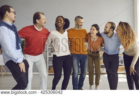 Group Of Happy Cheerful Diverse Friends Huddling, Laughing And Having Fun Together