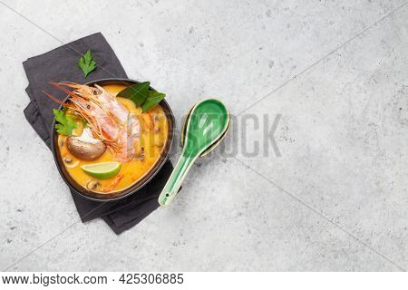 Tom Yum traditional Thai soup with seafood, mushrooms, coconut milk and hot spices. Top view with copy space