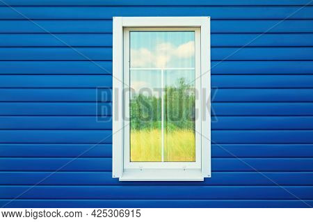 A Fragment Of The Wall Of The House, Sheathed With Blue Siding. There Is A Window With A White Frame