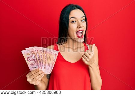 Young hispanic girl holding thai baht banknotes pointing thumb up to the side smiling happy with open mouth