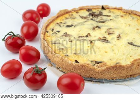 Closeup Studio Shot Of Freshly Baked Yellow French Salty Cake, Or Quiche With Mushrooms, Red Cherry