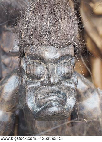 Russia, Sochi 06.06.2021. The Scary Face Of An Ethnic Figure Made Of Dark Wood. Decorative Figure In