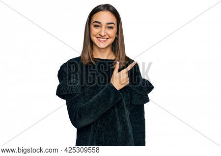 Beautiful brunette woman wearing elegant sweater cheerful with a smile of face pointing with hand and finger up to the side with happy and natural expression on face