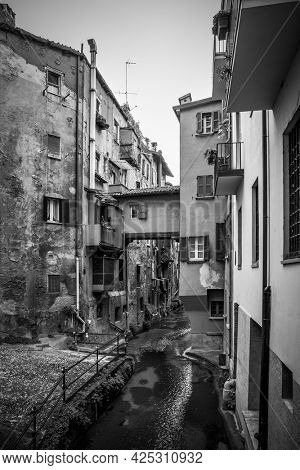 Secret canal in the old town of Bologna, Italy. Black and white urban photography, cityscape