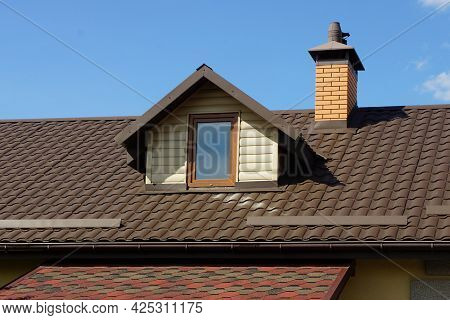 Attic Of A Private House Under A Brown Tiled Roof With A Window Against A Blue Sky
