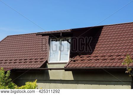 One White Attic Window On A Brown Tiled Roof Of A House Against A Blue Sky