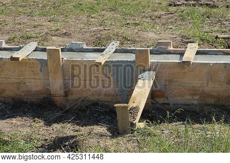 Foundation Of Gray Concrete And Wooden Brown Plank In The Formwork Outside In Green Grass