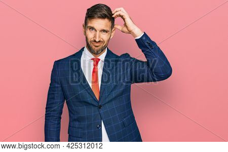 Handsome man with beard wearing business suit and tie confuse and wonder about question. uncertain with doubt, thinking with hand on head. pensive concept.