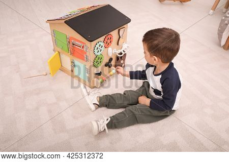 Little Boy Playing With Busy Board House On Floor In Room