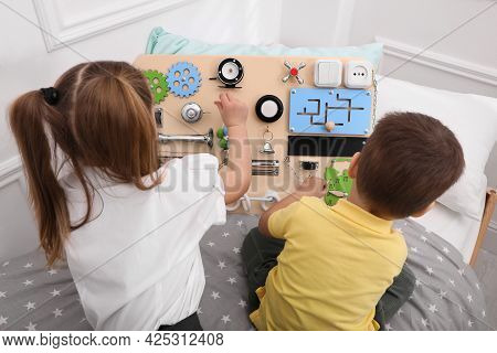 Little Boy And Girl Playing With Busy Board On Bed In Room