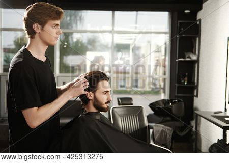 Hairstylist serving client at barbershop. Handsome brunet man visiting hairstylist in hairdressing saloon.