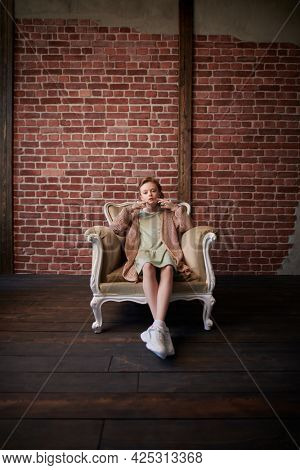 Kid's fashion. Full length portrait of a cute eight year old modern girl sitting in a vintage armchair in loft room.
