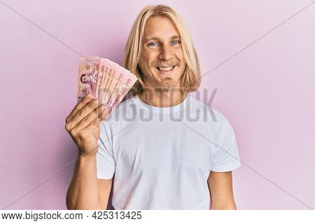 Caucasian young man with long hair holding 100 thai baht banknotes looking positive and happy standing and smiling with a confident smile showing teeth