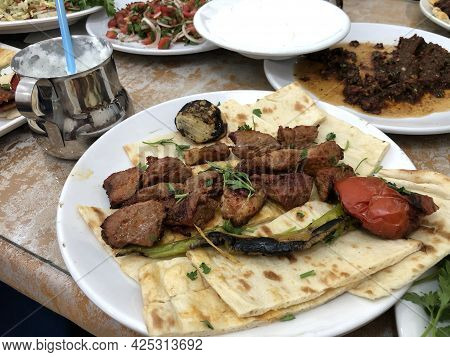 Fried Lamb Meat On Pita Bread. Traditional Turkish Or Middle Eastern Dinner With Fried Meat And Vege