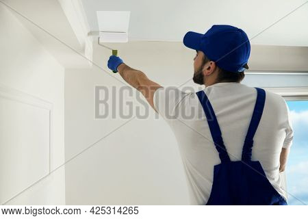 Handyman Painting Ceiling With White Dye Indoors, Back View