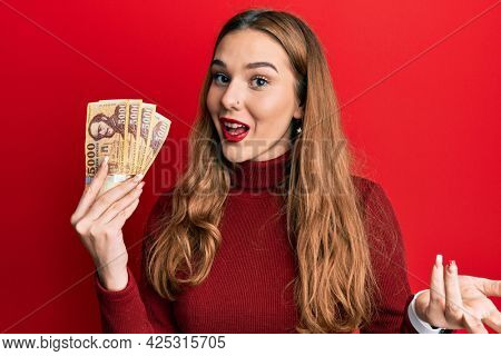 Young blonde woman holding 5000 hungarian forint banknotes celebrating achievement with happy smile and winner expression with raised hand
