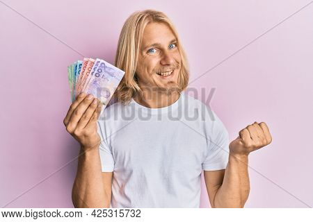 Caucasian young man with long hair holding thai baht banknotes screaming proud, celebrating victory and success very excited with raised arm