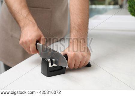 Man Sharpening Knife At White Table Indoors, Closeup