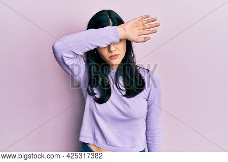 Young hispanic woman wearing casual clothes covering eyes with arm, looking serious and sad. sightless, hiding and rejection concept