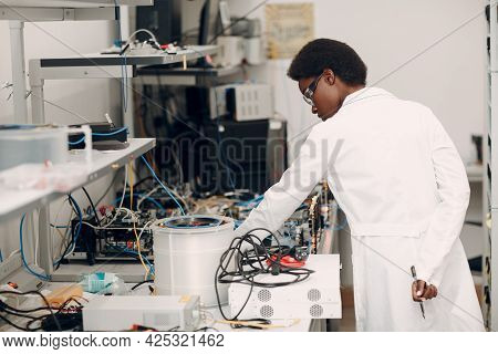 Scientist African American Woman Working In Laboratory And Single Photon Decoder Encoder Fiber Optic