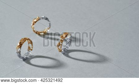 Elegant Clear Resin Rings With Half Golden And Silver Filling Standing On Gray Background, Widescree