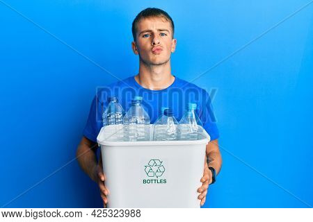 Young caucasian man holding recycling wastebasket with plastic bottles looking at the camera blowing a kiss being lovely and sexy. love expression.