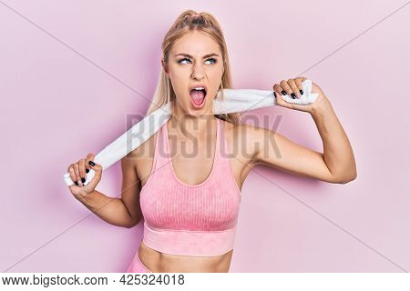 Young beautiful caucasian woman wearing sportswear and towel angry and mad screaming frustrated and furious, shouting with anger looking up.