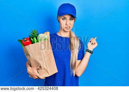 Young caucasian woman wearing courier uniform with groceries from supermarket pointing aside worried and nervous with forefinger, concerned and surprised expression