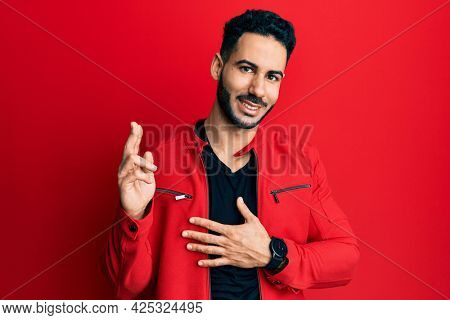 Young hispanic man wearing red leather jacket smiling swearing with hand on chest and fingers up, making a loyalty promise oath